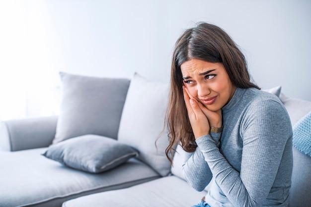 Porträt der jungen frau mit zahnschmerzen