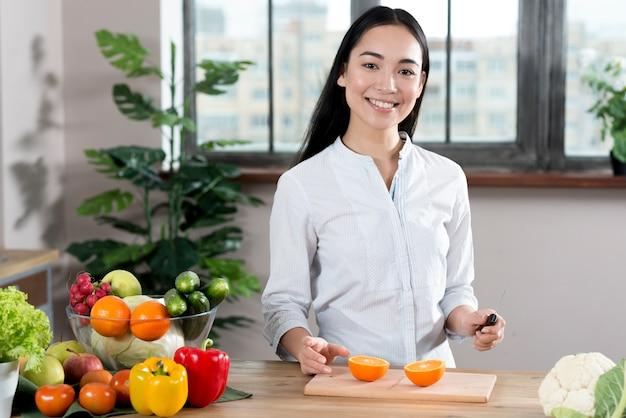 Porträt der jungen frau nahe küchentheke mit verschiedenen arten des gemüses und der früchte stehend