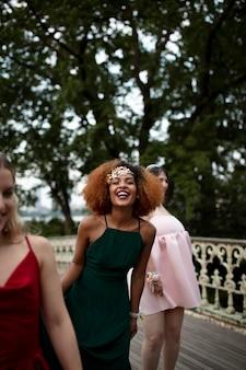 Porträt der jungen frau neben ihren freunden beim abschlussball