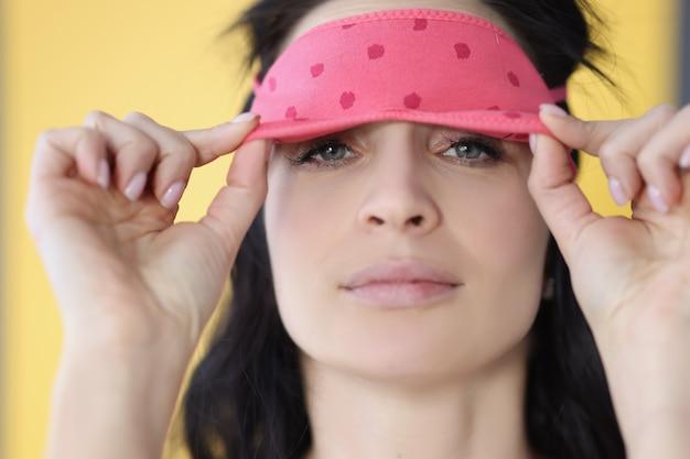 Porträt der jungen frau nimmt den augenschutz der schlafmaske vor hellem licht beim schlafen ab