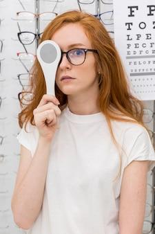 Porträt der jungen frau optikverschluss vor ihrem auge halten