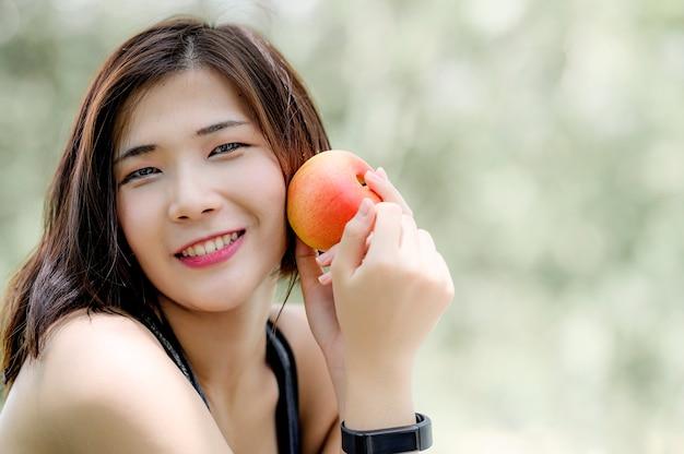 Porträt der jungen frau roten apfel halten, kamera lächelnd und betrachten