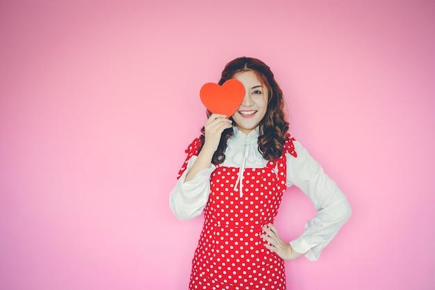 Porträt der jungen frau rotes herz vor ihren augen auf rosa hintergrund halten