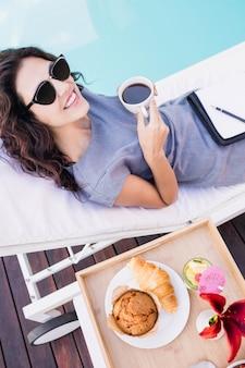 Porträt der jungen frau tasse tee trinkend und auf einem sonnenruhesessel nahe poolside entspannend