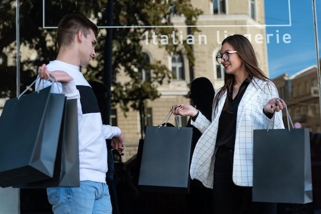 Porträt der jungen frau und des mannes mit einkaufstaschen. erfolgreiches einkaufskonzept. junges paar nach dem einkaufen. schwarzer freitag.