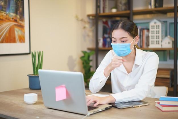 Porträt der jungen frau unter verwendung des laptops im café, das gesichtsschutzmaske trägt, um infektionskrankheiten zu verhindern