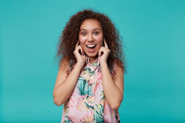 Porträt der jungen freudigen langhaarigen lockigen brünetten dame, die aufgeregt mit breitem lächeln schaut, während musik mit ohrhörern hört, lokalisiert auf blau