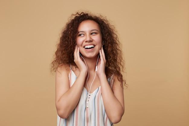 Porträt der jungen fröhlichen langhaarigen lockigen brünetten frau, die breit lächelt, während sie musik hört und hände zu ihren ohren hebt, auf beige stehend