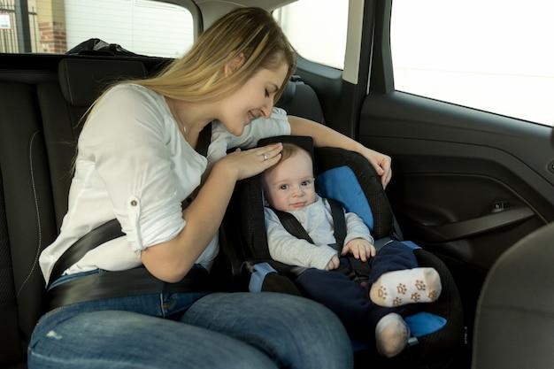Porträt der jungen fürsorglichen mutter mit ihrem baby auf dem rücksitz des autos