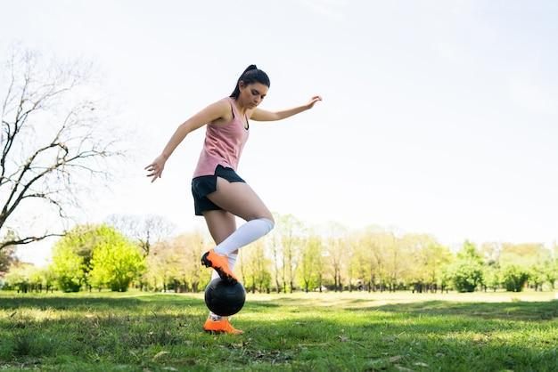 Porträt der jungen fußballspielerin, die um kegel läuft, während mit ball auf dem feld trainiert. sportkonzept.