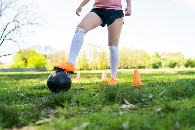 Porträt der jungen fußballspielerin, die um kegel läuft, während mit ball auf dem feld übt