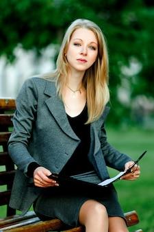 Porträt der jungen geschäftsdame, die auf bank mit dokumenten sitzt