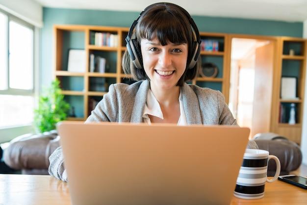 Porträt der jungen geschäftsfrau auf videoanruf mit laptop und kopfhörern. home-office-konzept. neuer normaler lebensstil.