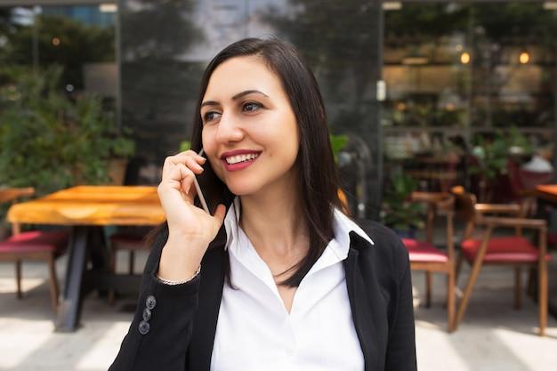 Porträt der jungen geschäftsfrau, die am handy im café spricht