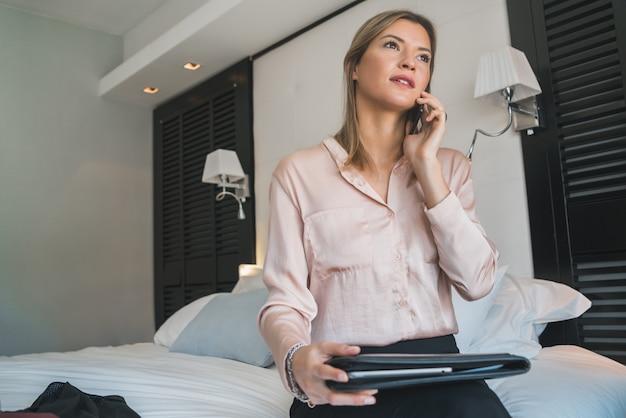 Porträt der jungen geschäftsfrau, die am telefon im hotelzimmer spricht. geschäftsreisekonzept.