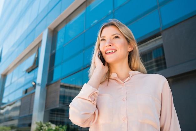 Porträt der jungen geschäftsfrau, die am telefon spricht, während außerhalb der bürogebäude steht. geschäfts- und erfolgskonzept.