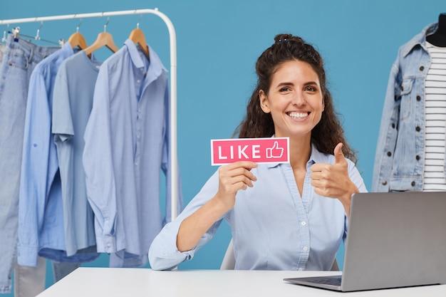 Porträt der jungen geschäftsfrau, die am tisch vor laptop sitzt und daumen oben im laden zeigt