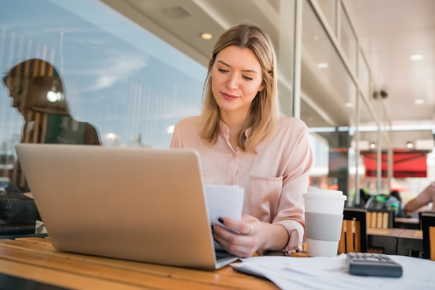 Porträt der jungen geschäftsfrau, die an ihrem laptop in einem café arbeitet. unternehmenskonzept.