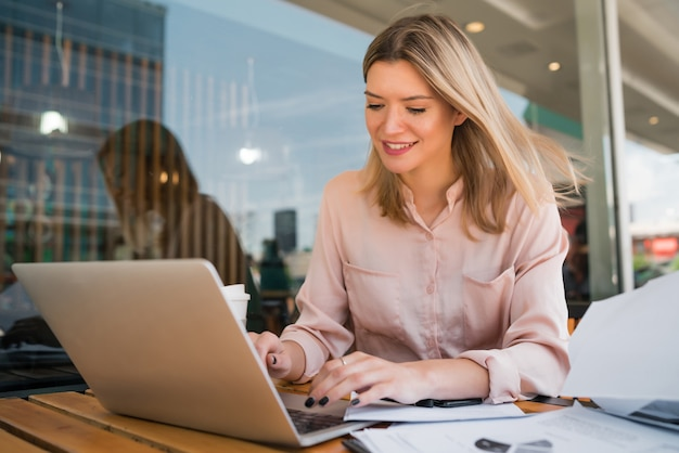 Porträt der jungen geschäftsfrau, die an ihrem laptop in einem café arbeitet.