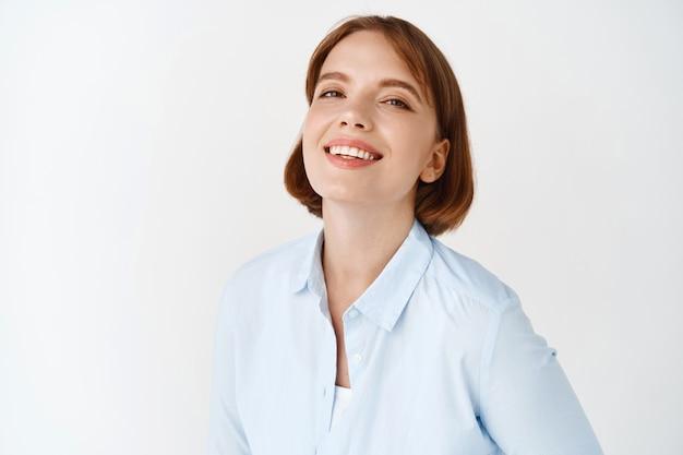 Porträt der jungen geschäftsfrau, die auf weißer wand lächelt. unternehmerin in bürobluse, motiviert und selbstbewusst stehend