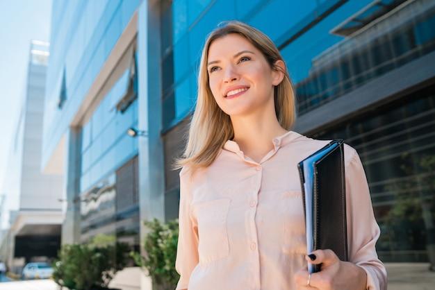 Porträt der jungen geschäftsfrau, die außerhalb der bürogebäude steht