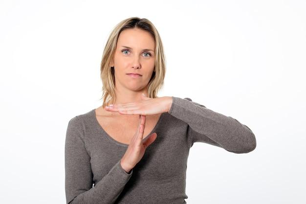 Porträt der jungen geschäftsfrau, die auszeitzeichen gestikuliert