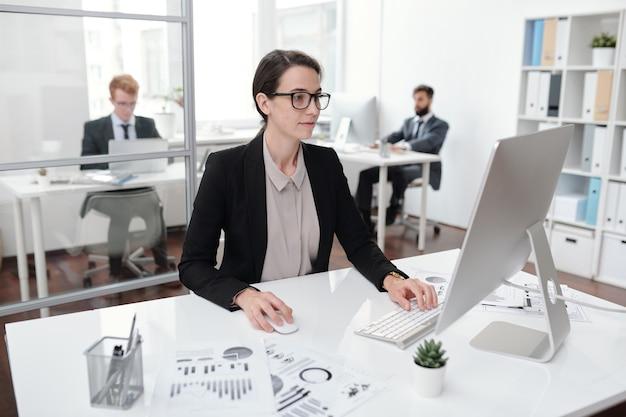 Porträt der jungen geschäftsfrau, die brille unter verwendung des pc sitzt, der am schreibtisch im büro-, buchhalter- oder managerkonzept sitzt