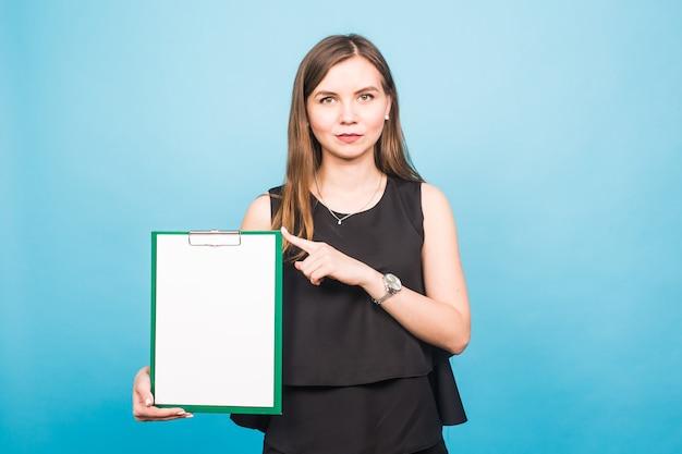 Porträt der jungen geschäftsfrau, die eine leere fahne hält. bild auf blauem studiohintergrund. business- und lifestyle-konzept.