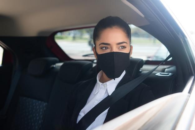 Porträt der jungen geschäftsfrau, die gesichtsmaske auf ihrem weg zur arbeit in einem taxi trägt