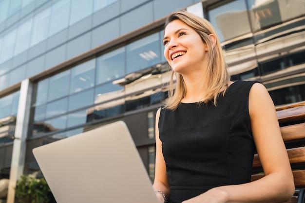 Porträt der jungen geschäftsfrau, die ihren laptop benutzt, während draußen an der straße sitzt. unternehmenskonzept.