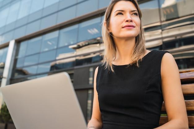 Porträt der jungen geschäftsfrau, die ihren laptop benutzt, während sie draußen an der straße sitzt. unternehmenskonzept.