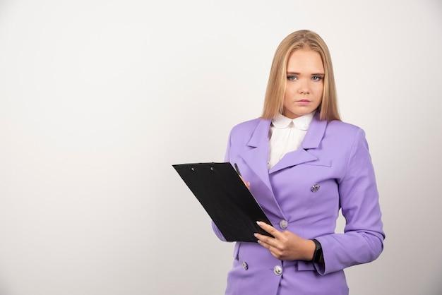 Porträt der jungen geschäftsfrau, die klemmbrett steht und hält.