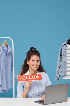 Porträt der jungen geschäftsfrau, die lächelt und hält, folgen sie plakat, das sie sagt, um ihrem online-shop zu folgen