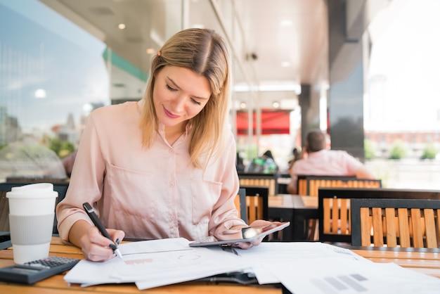 Porträt der jungen geschäftsfrau, die mit einem digitalen tablett am kaffeehaus arbeitet. unternehmenskonzept.