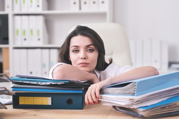 Porträt der jungen geschäftsfrau, die mit papierkram erschöpft ist, der auf ordnern mit arbeitspapieren im büro stützt