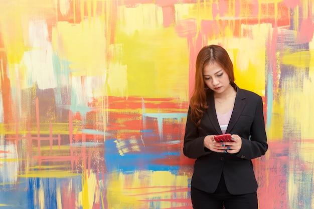 Porträt der jungen geschäftsfrau, die smartphone verwendet. drahtlose verbindungstechnik