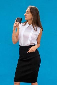 Porträt der jungen geschäftsfrau, die tasse kaffee lokalisiert auf blau hält