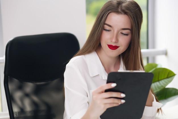 Porträt der jungen geschäftsfrau, die weißes hemd trägt, das im modernen büro mit laptop sitzt