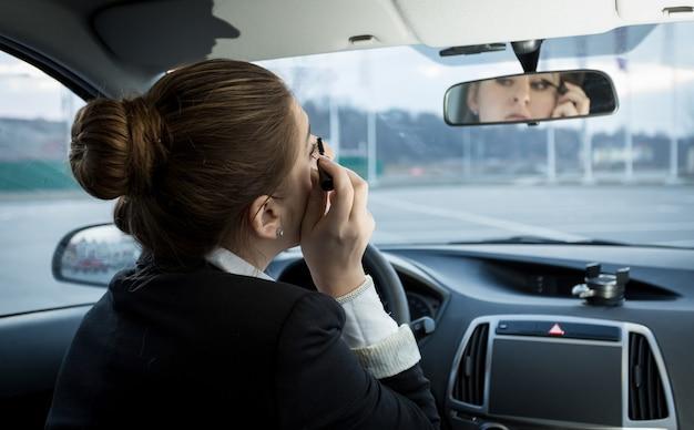 Porträt der jungen geschäftsfrau, die wimperntusche im auto anwendet