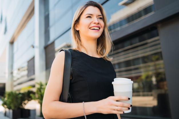 Porträt der jungen geschäftsfrau, die zur arbeit geht, während kaffee zum mitnehmen trinkt. geschäfts- und erfolgskonzept.