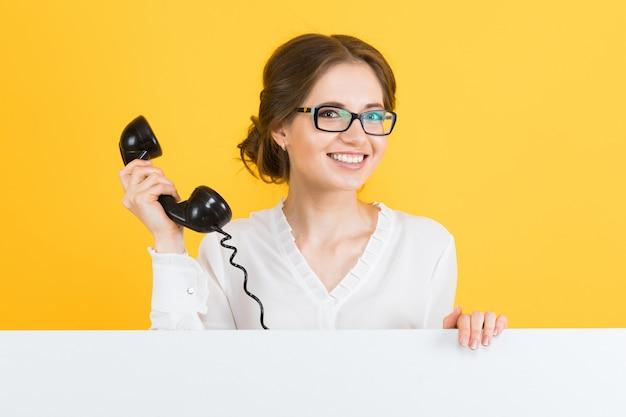 Porträt der jungen geschäftsfrau mit dem telefon, das leere anschlagtafel auf gelber wand zeigt
