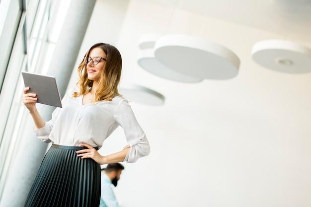 Porträt der jungen geschäftsfrau stehende wirth tablette im büro durch fenster