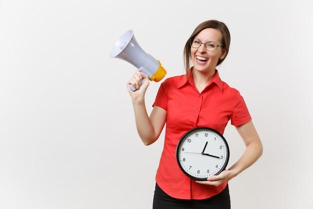 Porträt der jungen geschäftslehrerfrau im roten hemd, die runde uhr hält, schreit im megaphon, verkündet rabattverkauf, lokalisiert auf weißem hintergrund. heiße neuigkeiten, kommunikationskonzept.. beeilt euch, leute