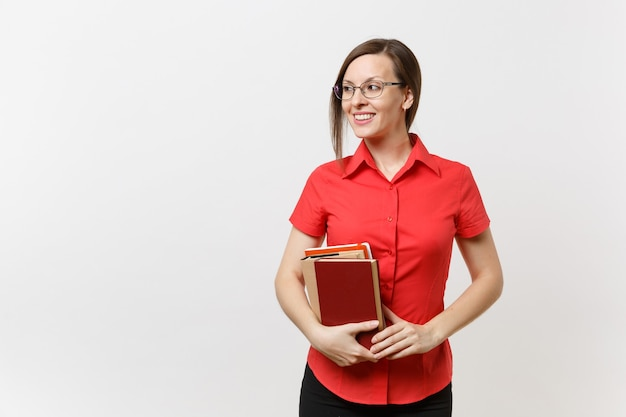 Porträt der jungen geschäftslehrerfrau im roten hemd, im rock und in den gläsern, die beiseite schauen und bücher in den händen halten lokalisiert auf weißem hintergrund. bildung oder lehre im hochschulkonzept.