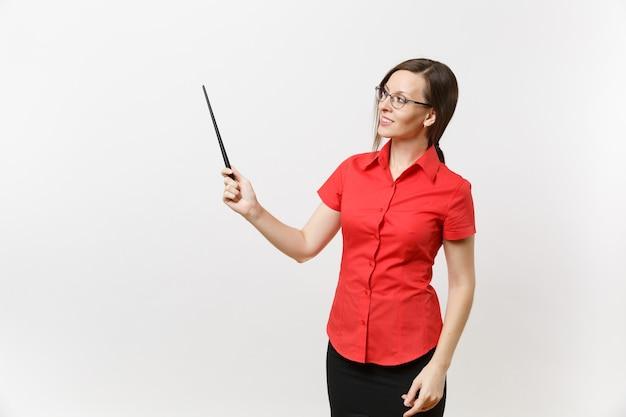 Porträt der jungen geschäftslehrerfrau in den roten hemdrockgläsern, die hölzernen klassenzimmerzeiger auf dem kopienraum lokalisiert auf weißem hintergrund halten. bildungsunterricht im hochschulkonzept.