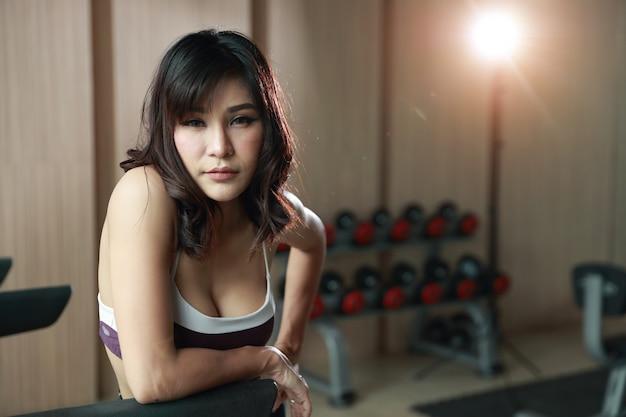 Porträt der jungen gesunden und sportlichen asiatischen frau, die eine pause nach übung in der turnhalle macht