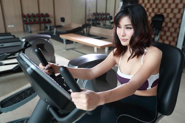 Porträt der jungen gesunden und sportlichen frau, die übungsmaschine in der turnhalle verwendet