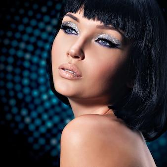 Porträt der jungen glamourfrau mit einem hellen make-up der augen - kunsthintergrund
