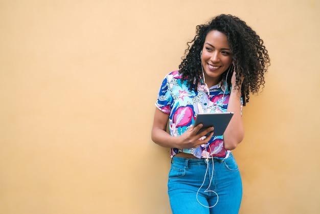 Porträt der jungen glücklichen afroamerikanischen lateinischen frau, die musik auf ihrem digitalen tablett hört. technologiekonzept.
