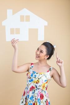 Porträt der jungen glücklichen aufgeregten asiatin, die papierhaus hält